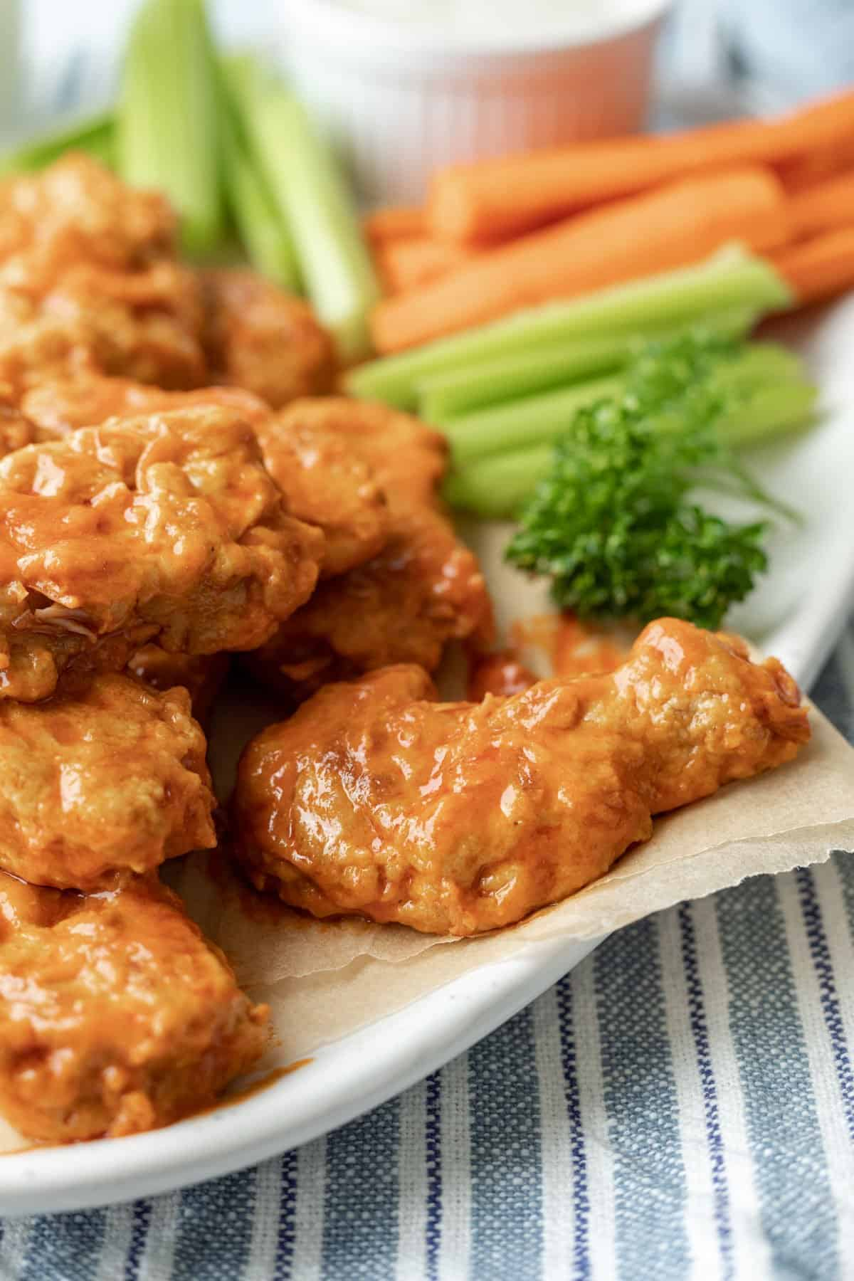 close up photo showing texture of steamed seitan wings covered in buffalo sauce.