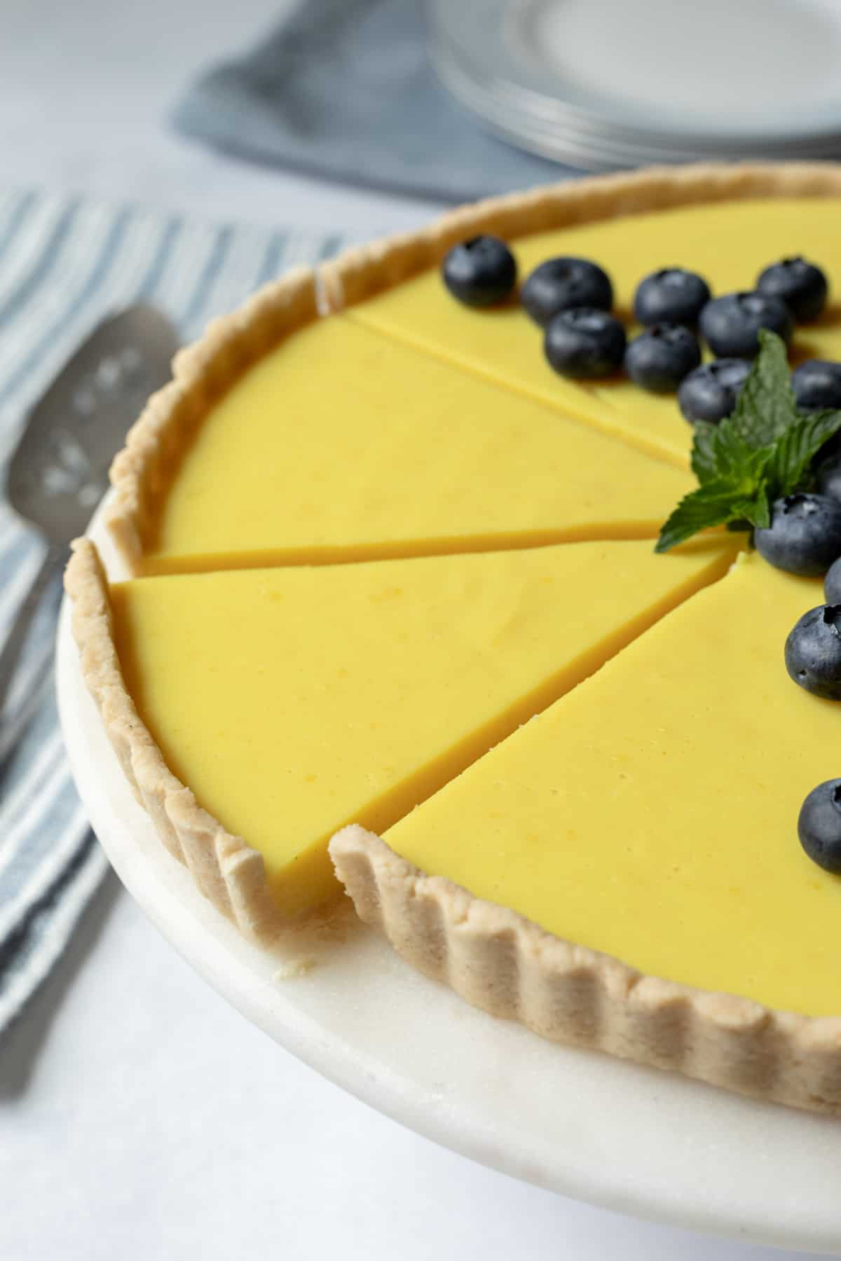 a vegan lemon tart decorated with blueberries and mint.