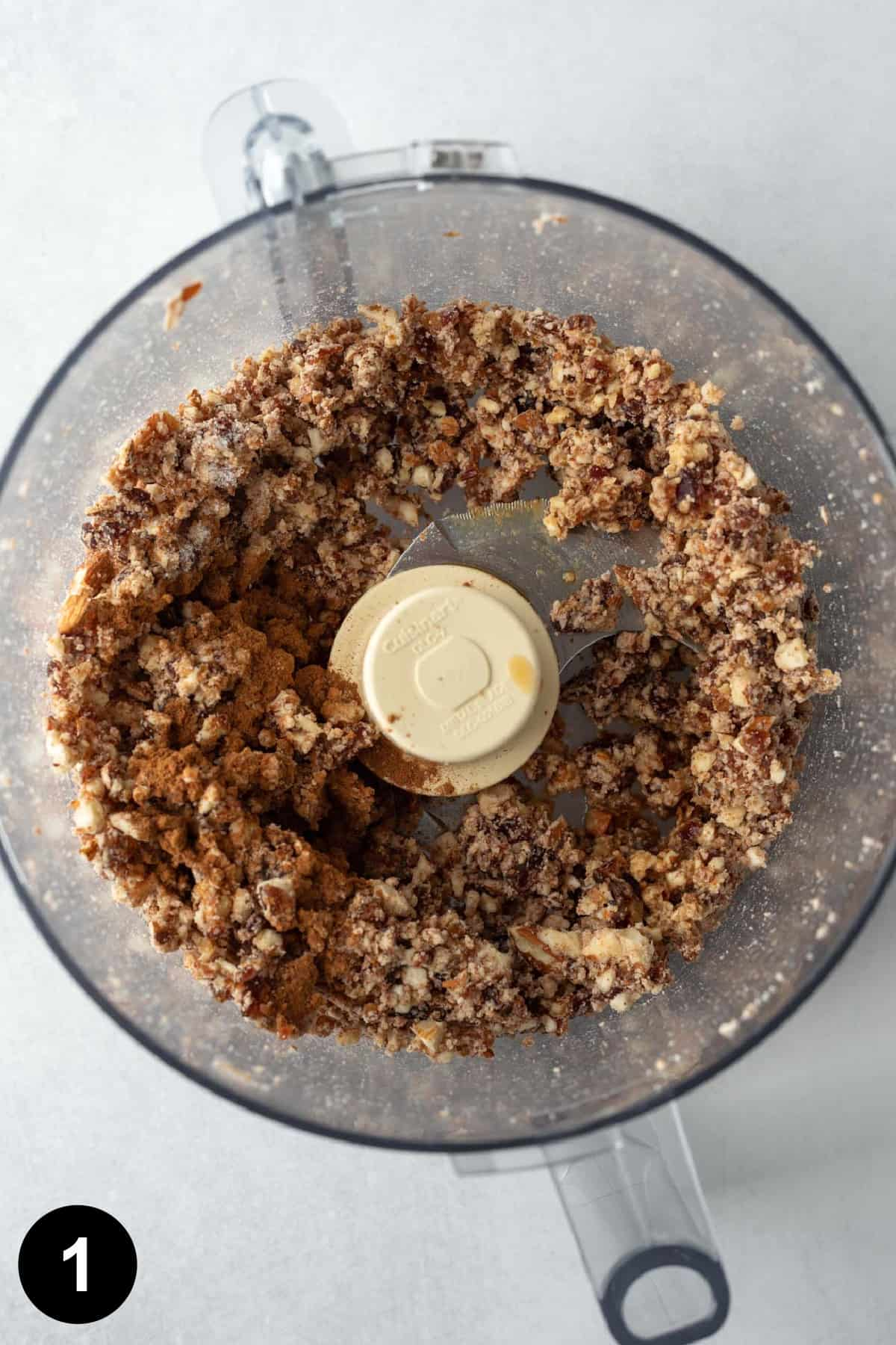 date, nut, and almond pulp mixture inside the bowl of a food processor.