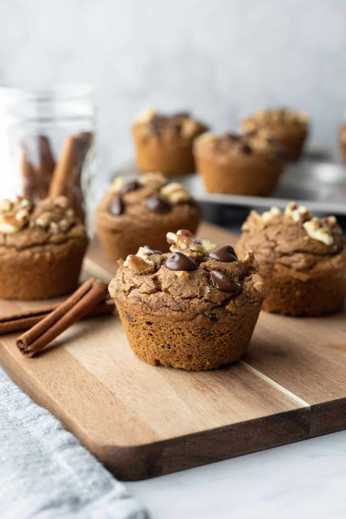 pumpkin spice muffins with walnuts and chocolate chips on a wood board.