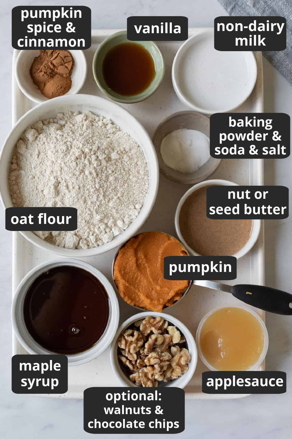 labeled photo of the ingredients needed to make oat flour pumpkin muffins.