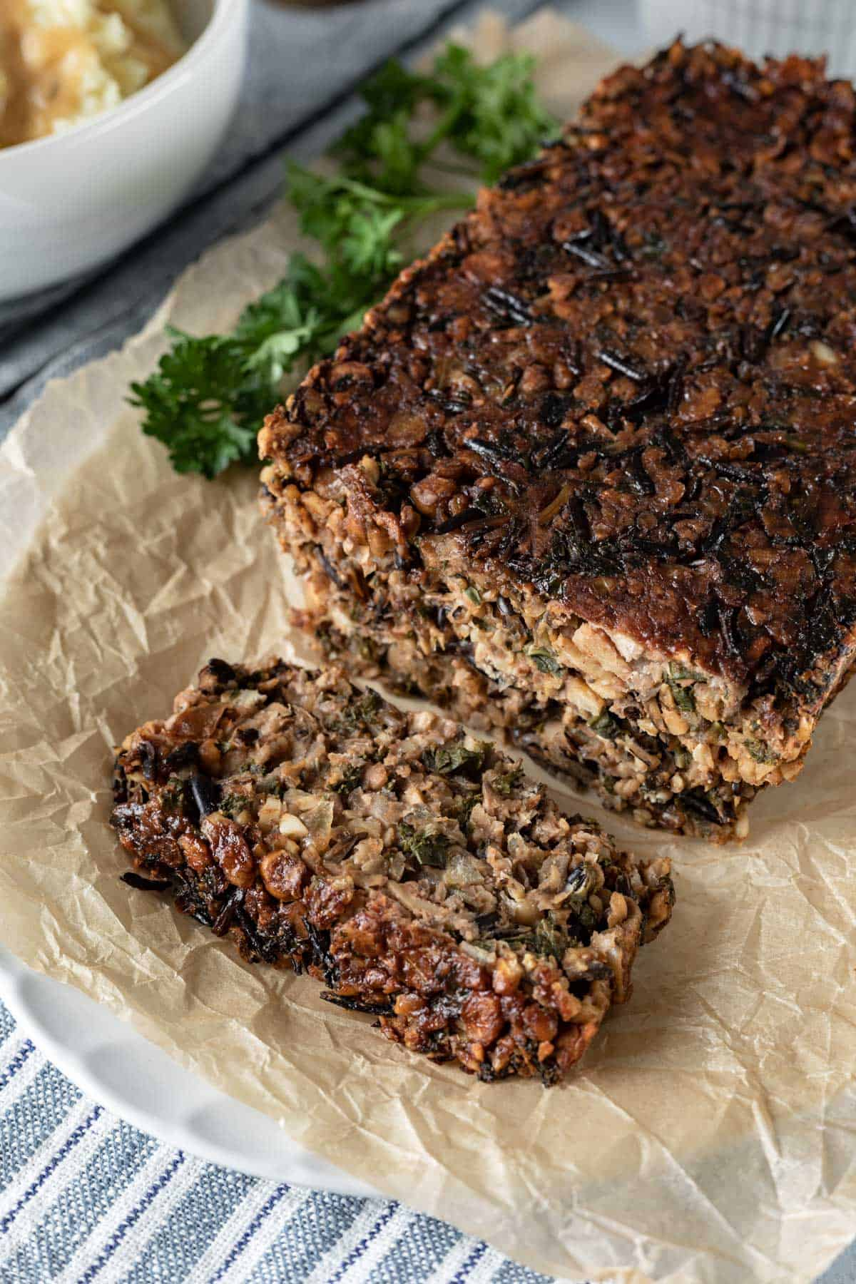 chunky vegan meatloaf filled with chickpeas, wild rice, and veggies on a white platter.