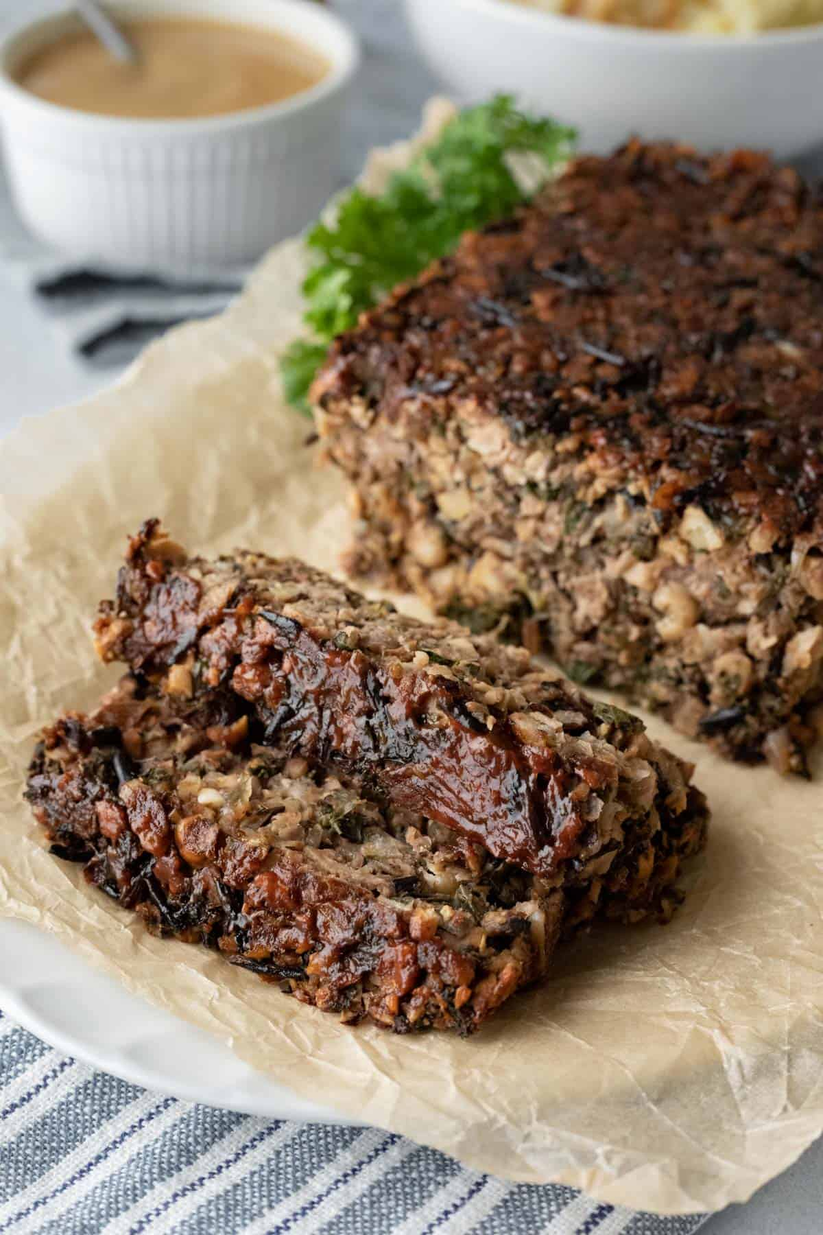 hearty wild rice chickpea meatloaf on a serving platter with 2 slices cut.