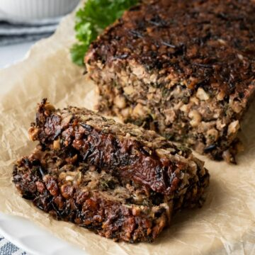 two slices of chickpea meatloaf with glaze resting on parchment paper.